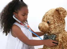 Adorable Little Playing Doctor To A Teddy Bear Over White. Shot with the Canon 20D.